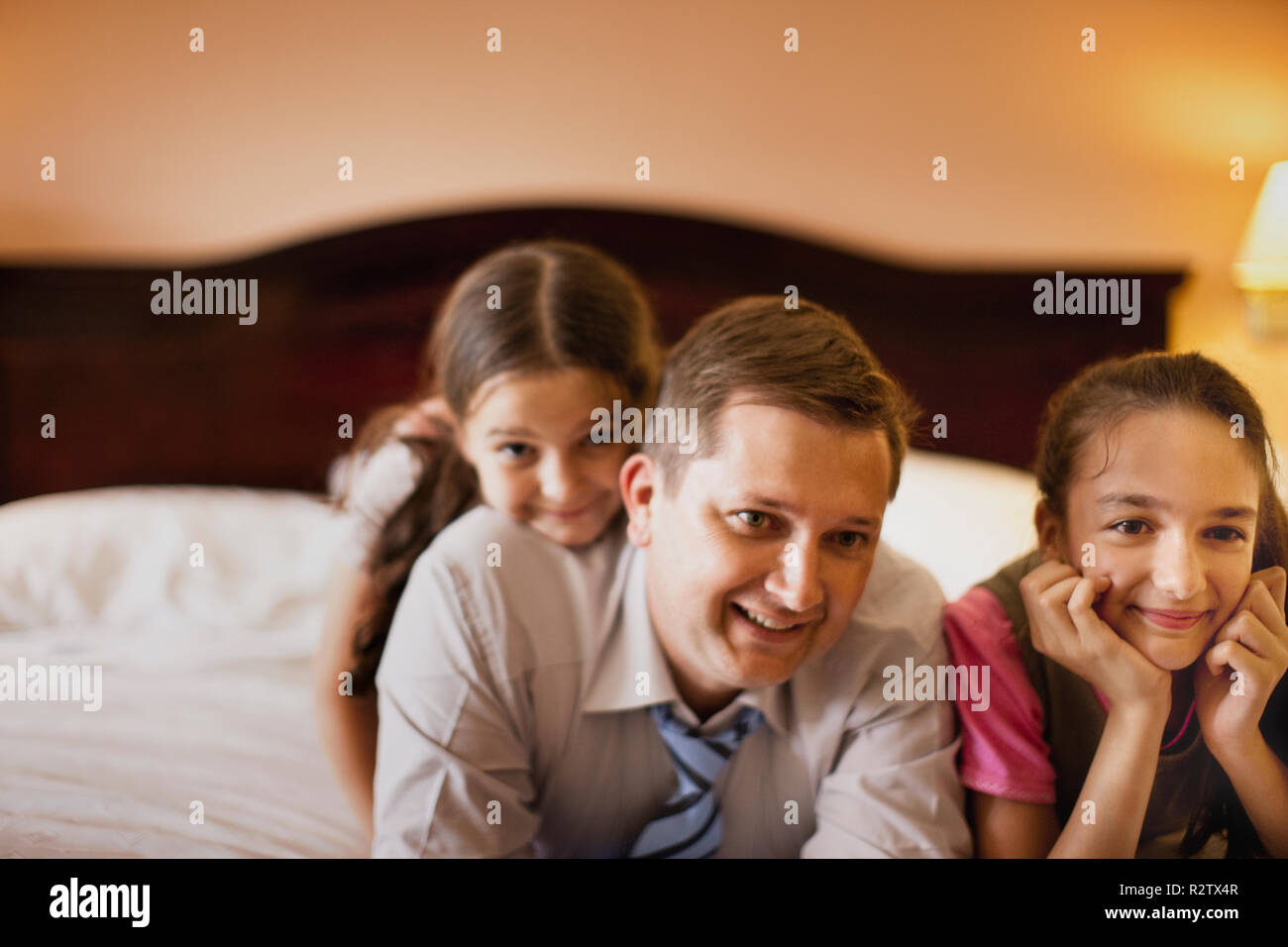 Two girls and their father relaxing on hotel bed. - Stock Image