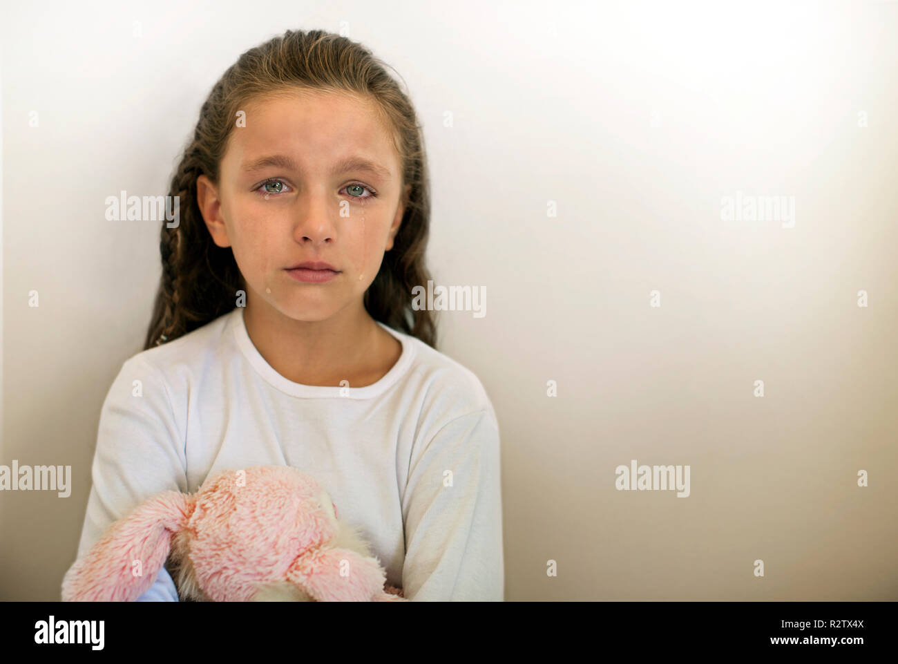Portrait of young girl crying, holding soft toy. - Stock Image