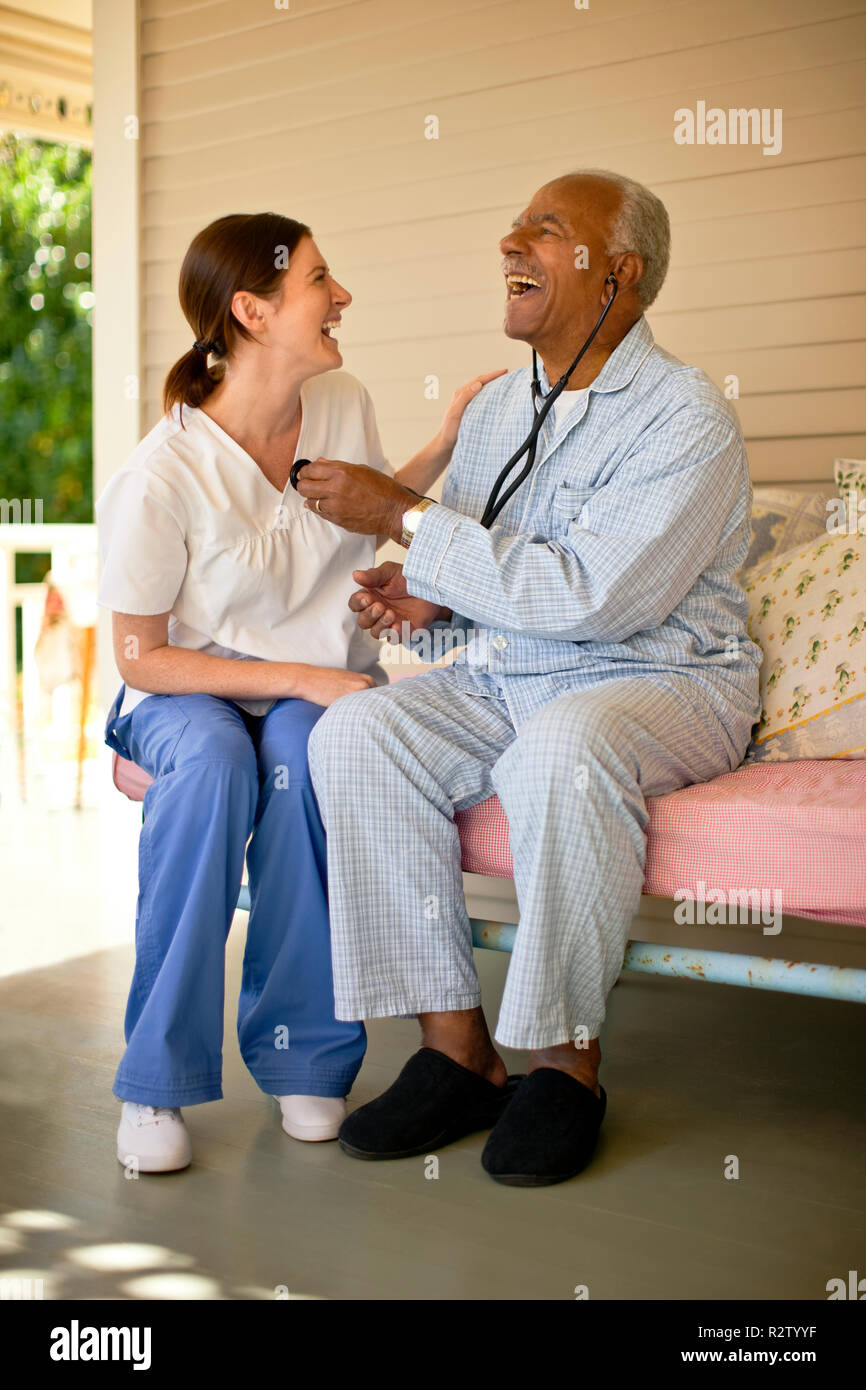 Elderly patient laughing while listening to the nurse's chest with stethoscope. Stock Photo