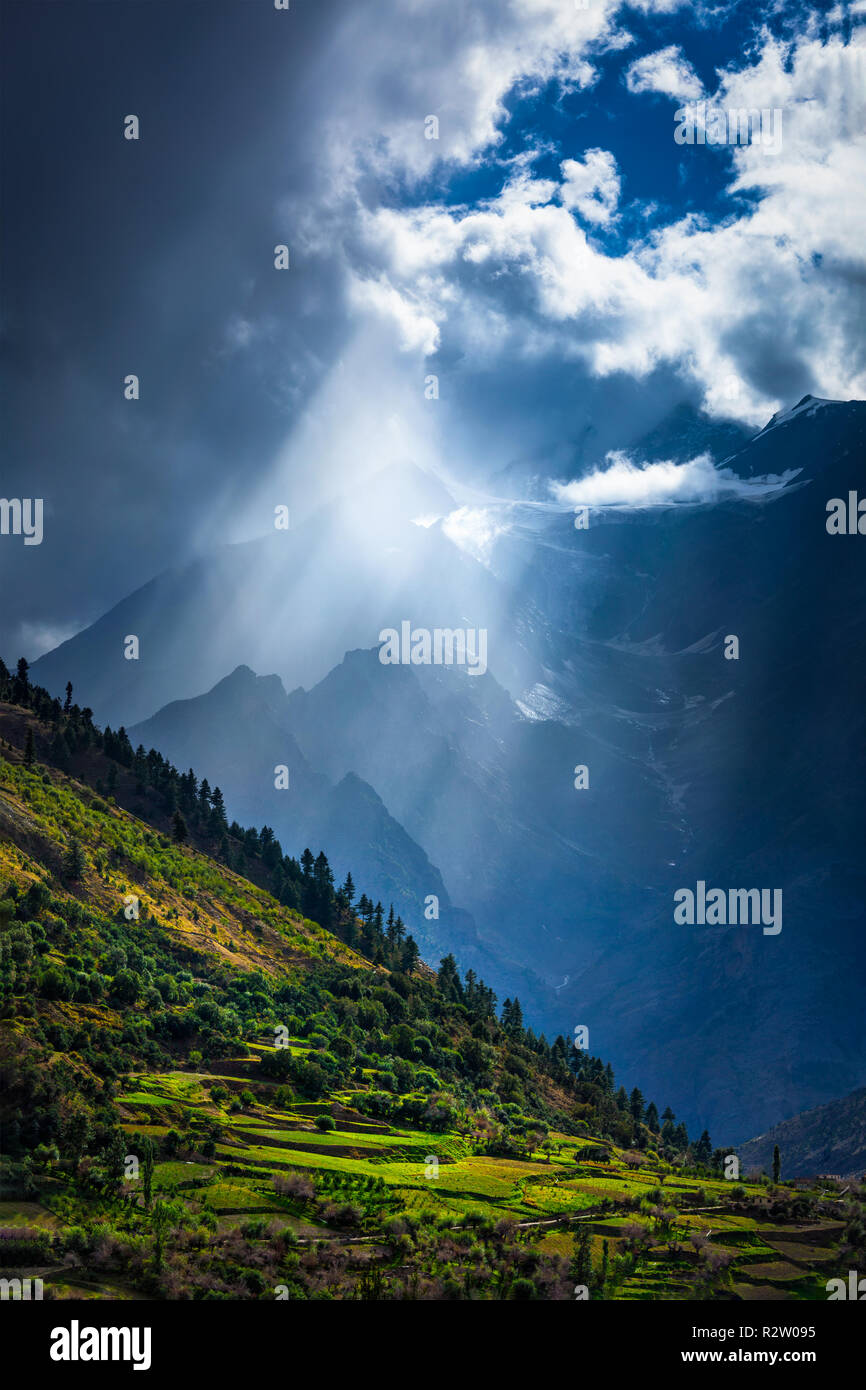 Sun rays through clouds in Himalayan valley in Himalayas - Stock Image