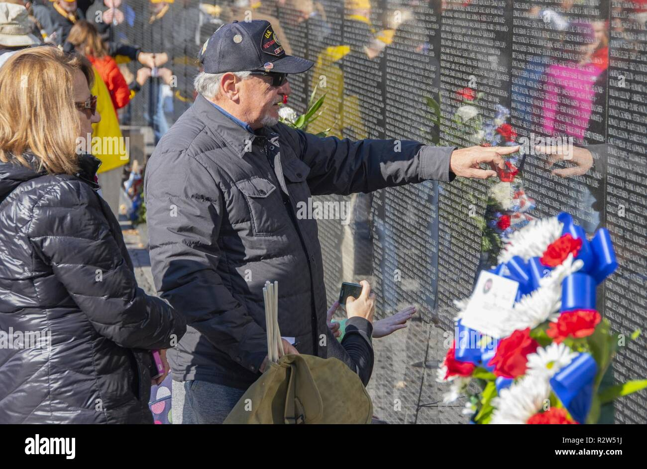 a3368428f6f A visitor to the Vietnam Veterans Memorial points to a name on one of its  polished black granite panels in Washington