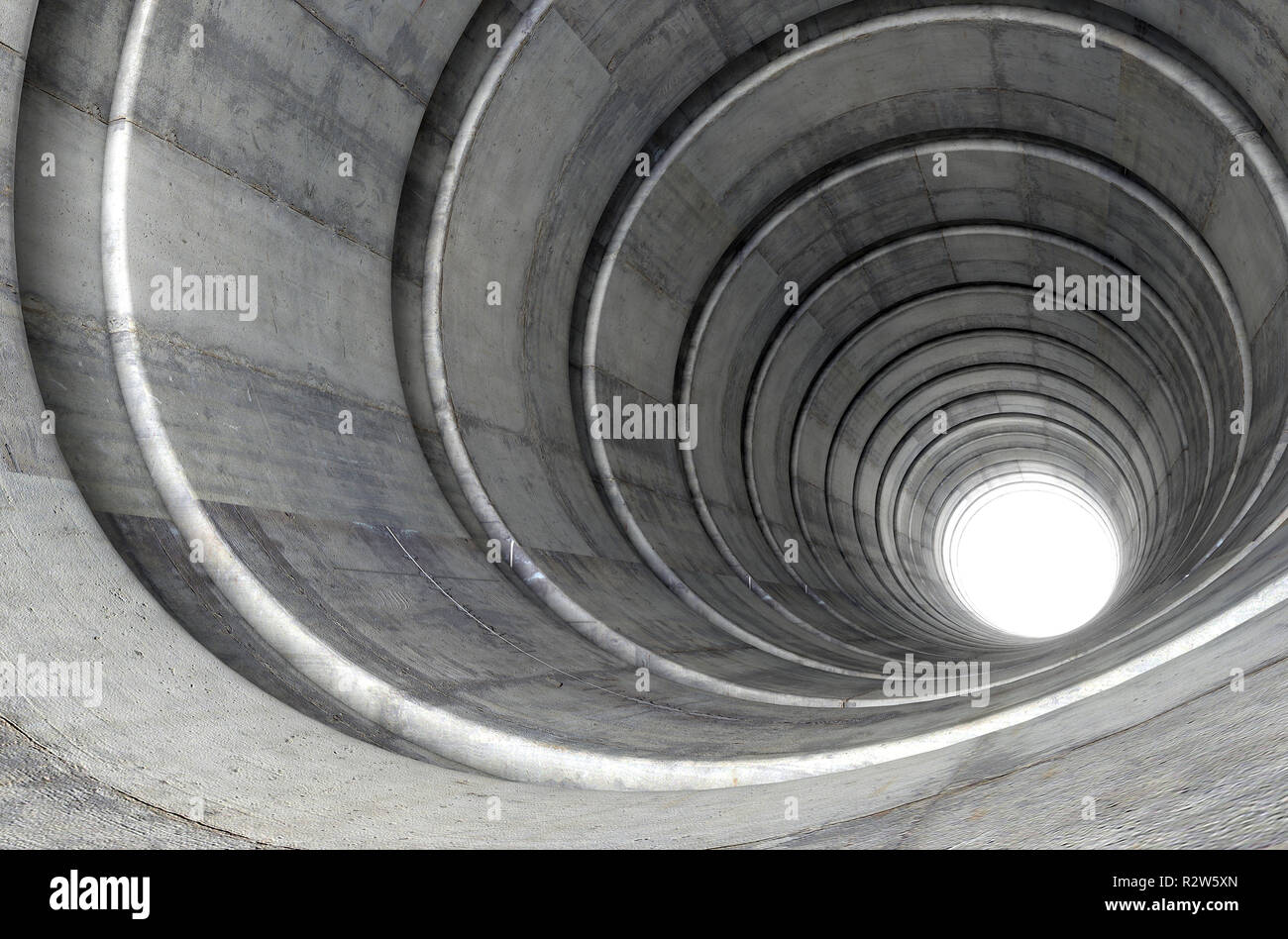 A look down a concrete tunnel made out of circular geometric shapes with a light in the distance at the far end - 3D render Stock Photo
