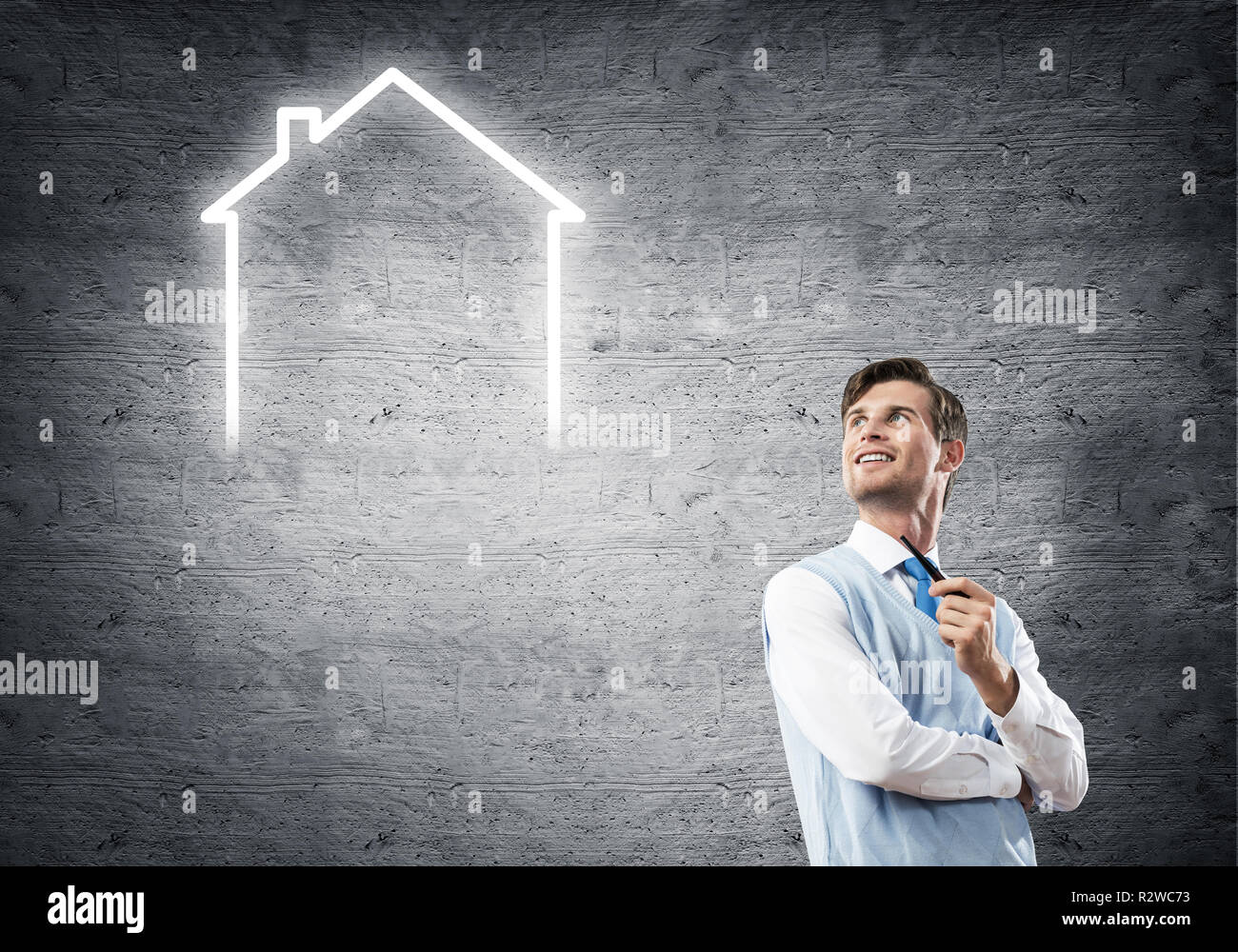 Elegant banker wearing red tie and house sign as banking concept - Stock Image