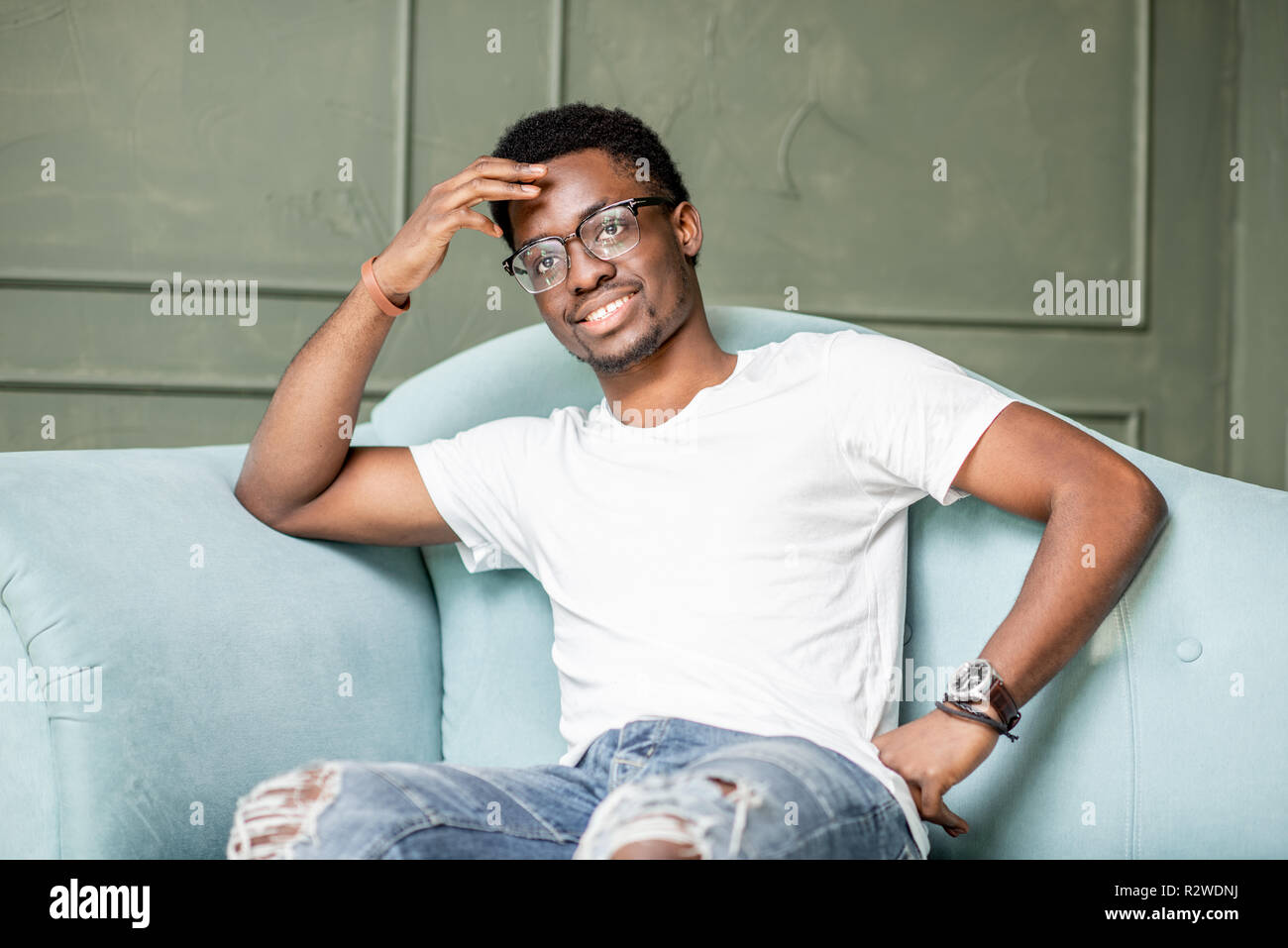 Portrait of a young afro ethnicity man sitting on the couch during the psychological session with psychologist in the office - Stock Image