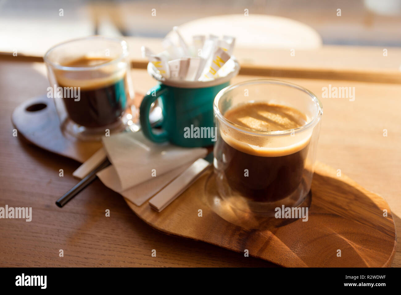 Wooden tray with two cups of coffee on the table in front of the window - Stock Image