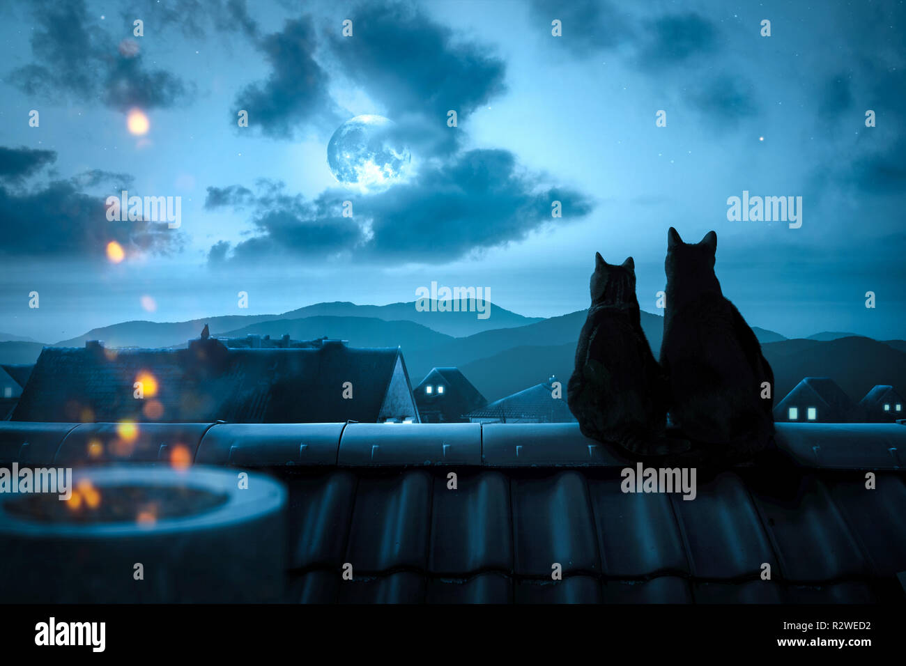 Cats watching the full moon on a rooftop - Stock Image
