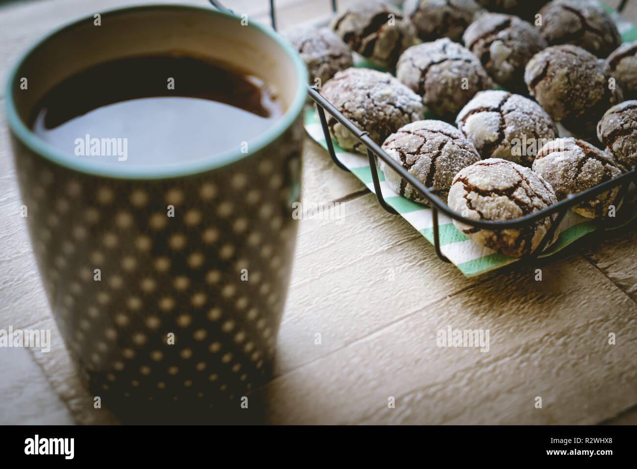Chocolate crinkle cookies in a basket with a cup of tea on a wooden table. Close up view. Landscape format. - Stock Image