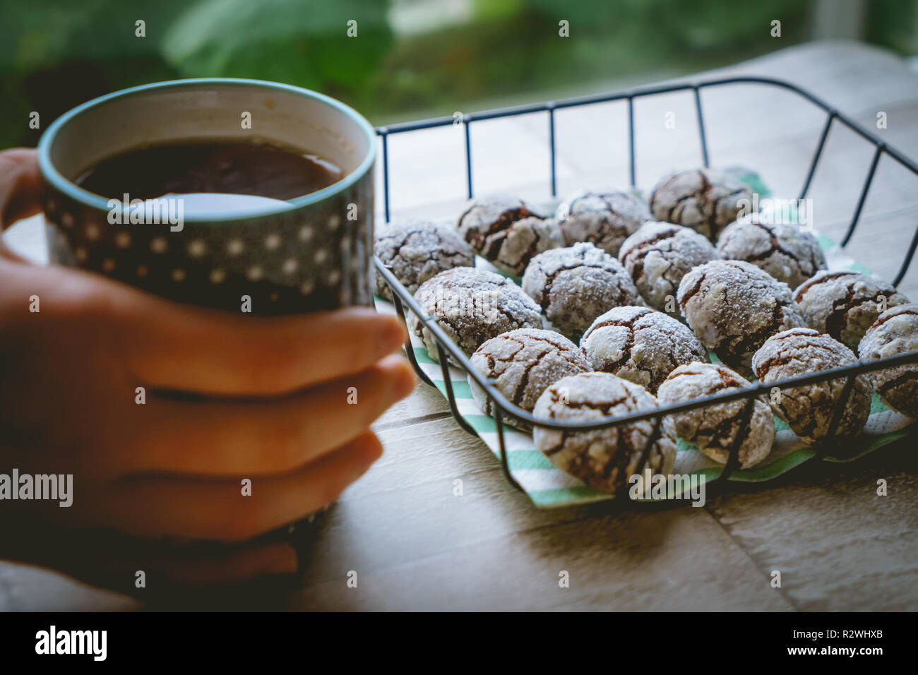 Chocolate crinkle cookies in a basket with a cup of tea hold by hands on a wooden table. Close up view. Landscape format. - Stock Image