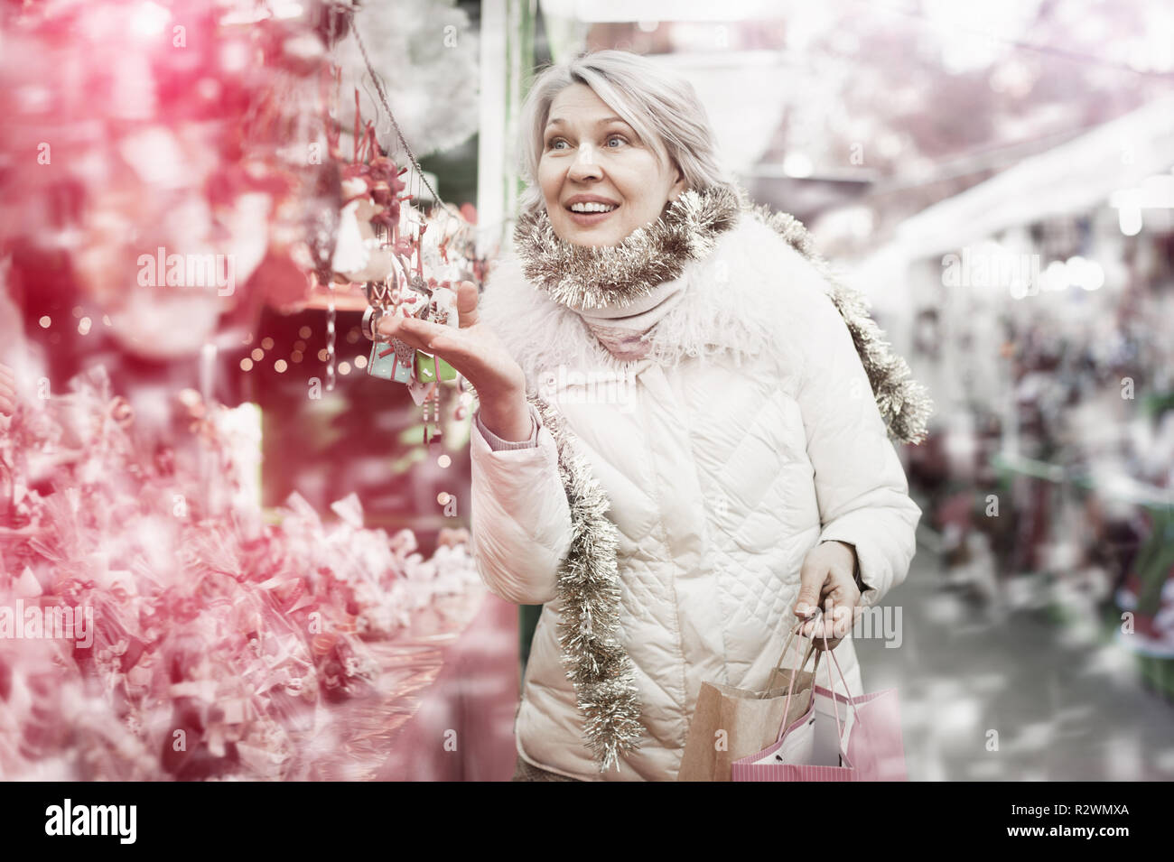 Smiling woman is buying Christmas ornamentals in the market outdoor. - Stock Image