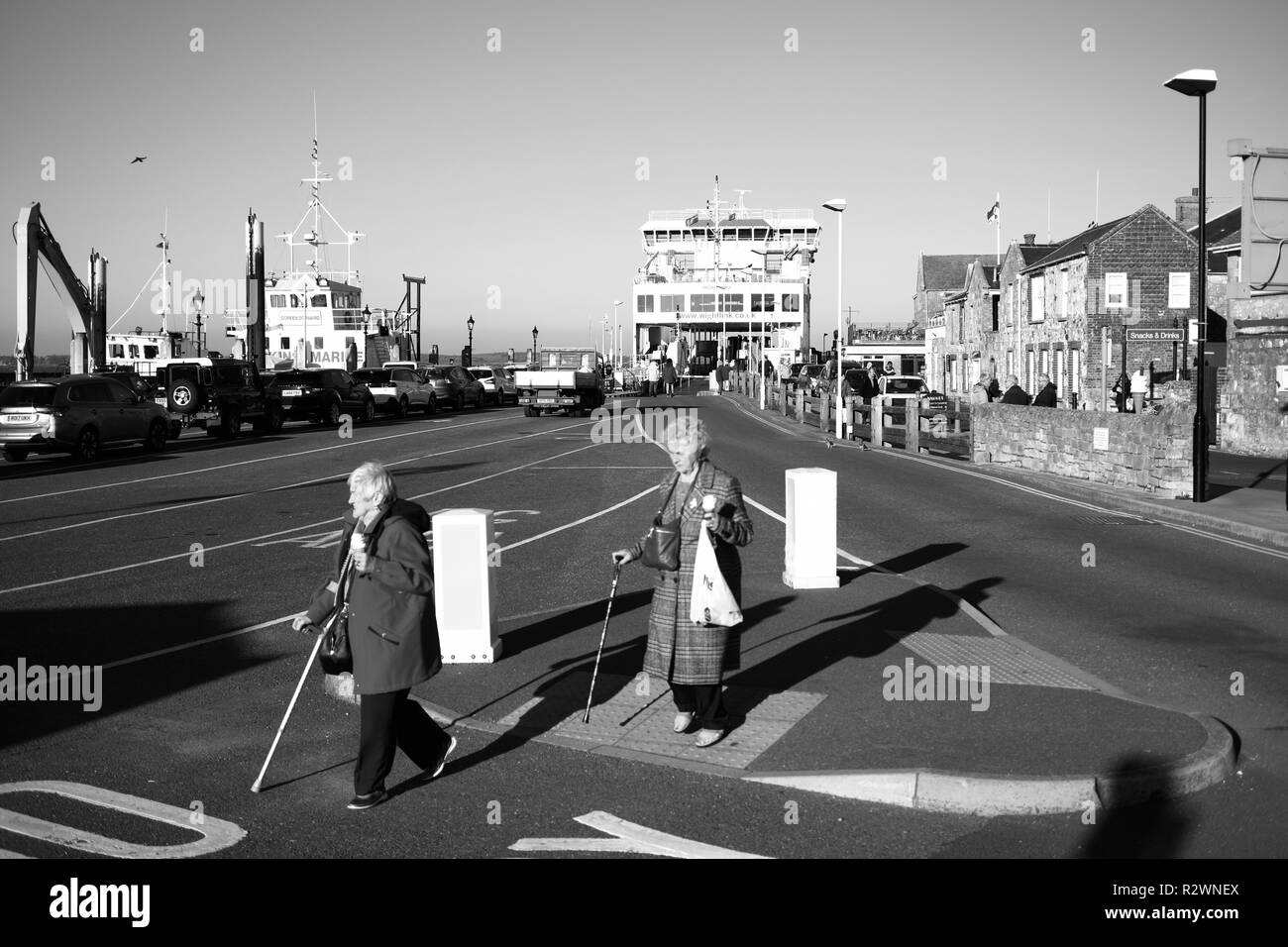 Two retired old Ladies crossing traffic island using sticks and carrying ice cream cones in their hands at Yarmouth Isle of Wight ferry park terminal - Stock Image