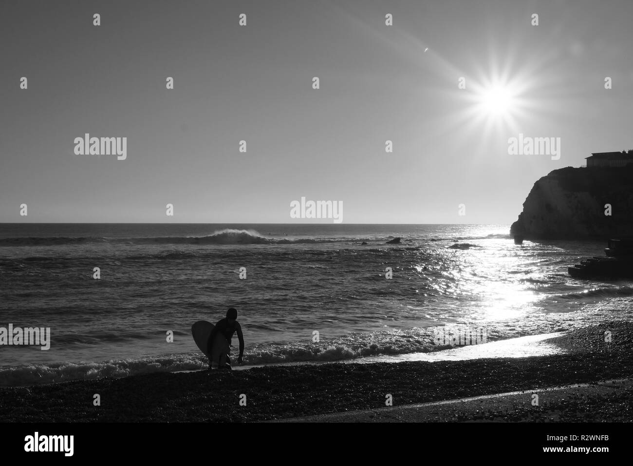 A surfer exits the water walking up the beach carrying his surf board at Freshwater Bay Isle of Wight. A bright sun shines on the wintery scene - Stock Image