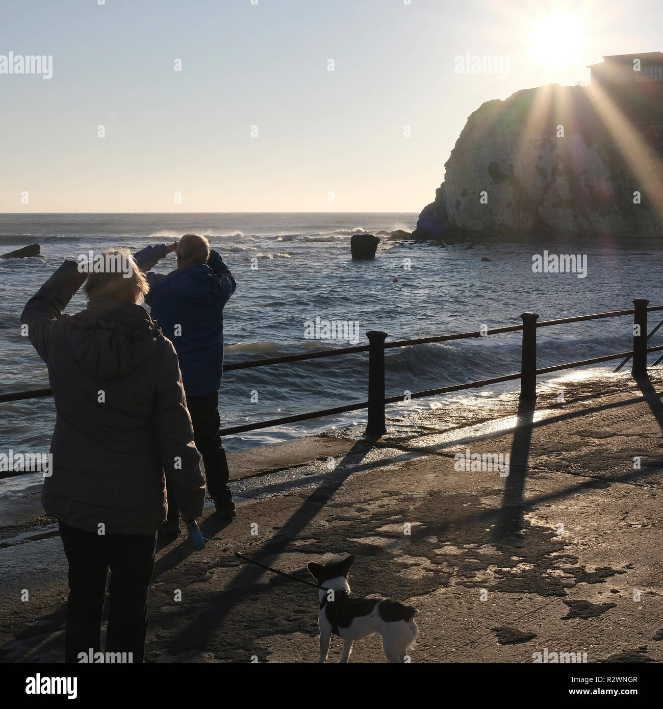 Afternoon walkers stop to watch the surfers on the horizon at Freshwater Bay Isle of Wight - Stock Image