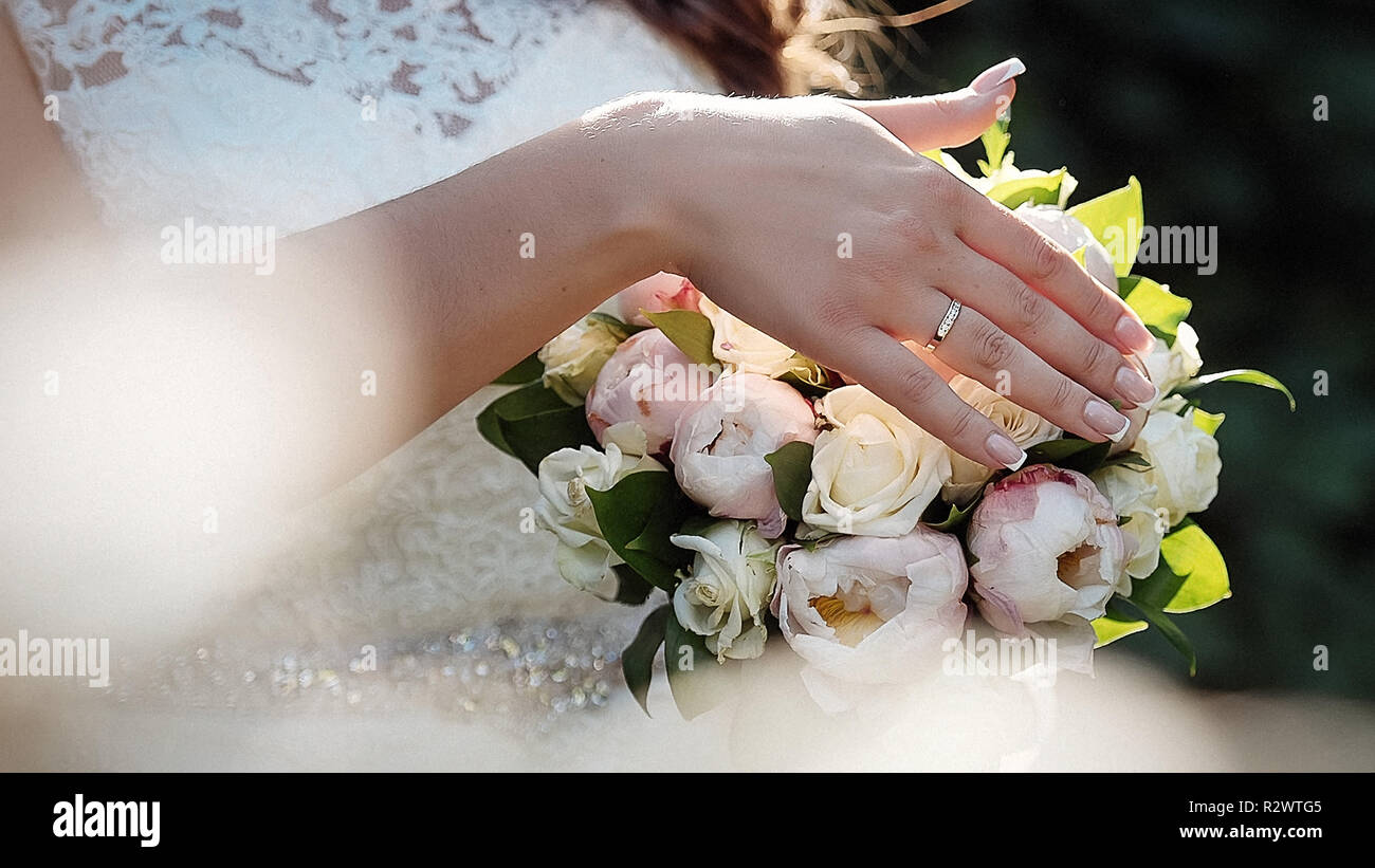 Beautiful bride holds wedding bouquet close up - Stock Image
