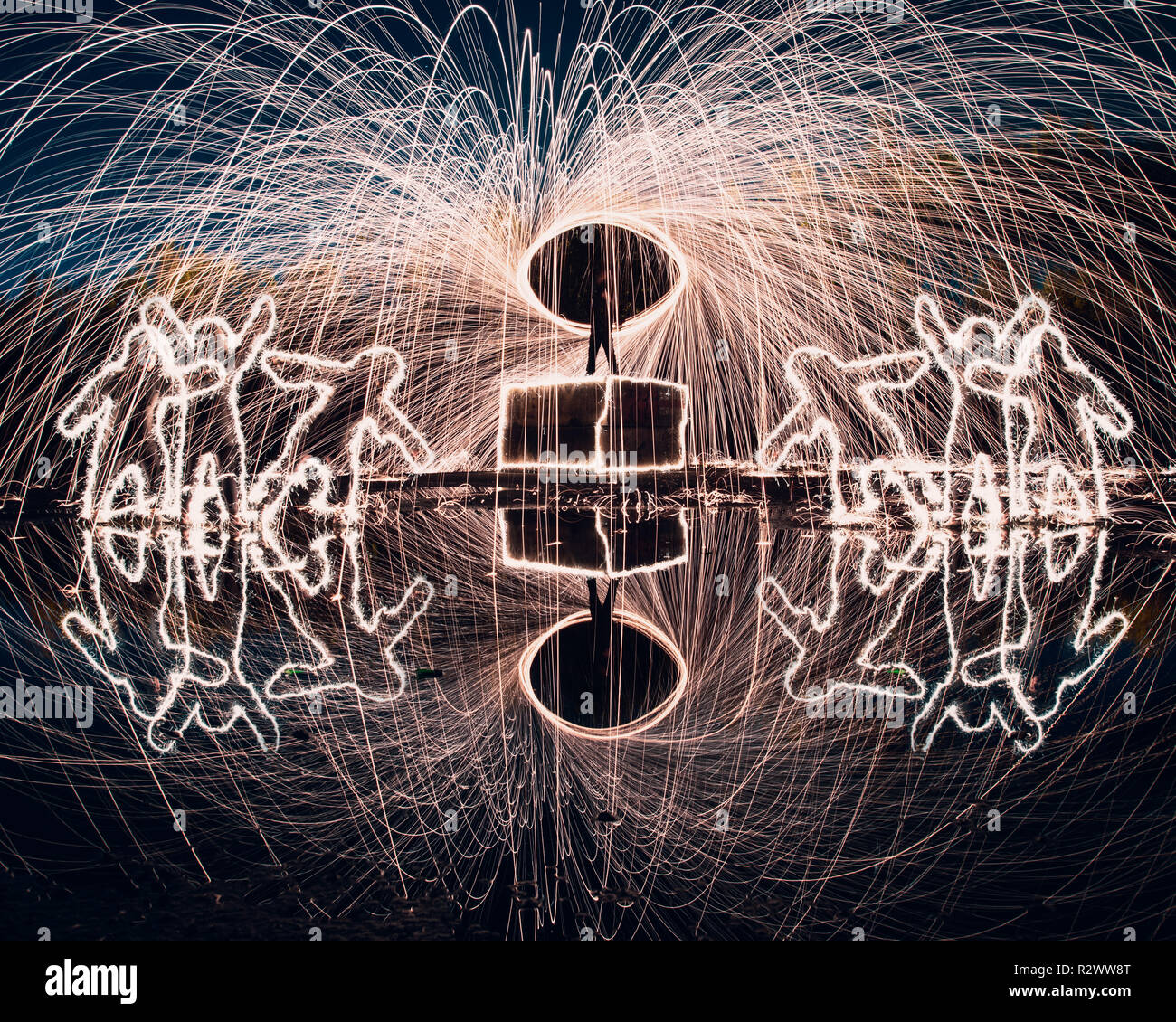 Steel wool spinning and light painting with reflections and people shaped from sparklers Stock Photo