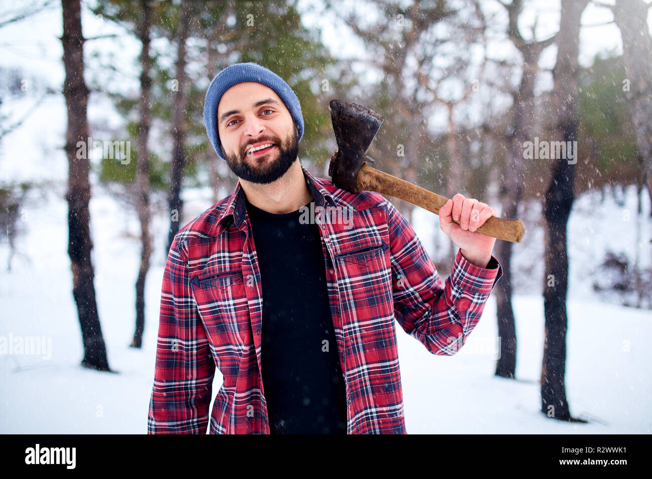 53fc12f52f1 Bearded hipster man in a winter snowy forest with axe on a shoulder.  Woodman standing