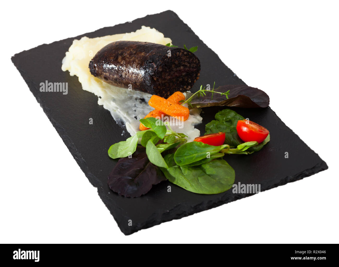 Fried morcilla (blood sausage with rice) served on white plate with pureed potatoes, vegetables and aromatic herbs. Isolated over white background - Stock Image