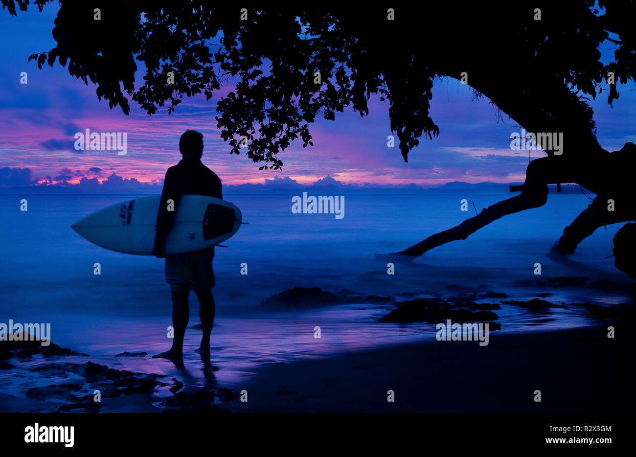 Surfer silhouettes at sunset, South Siberut, Indonesia. - Stock Image