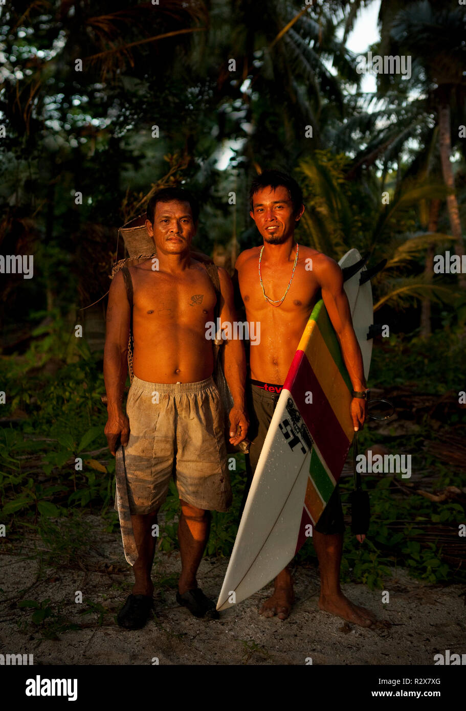 Surf guide Ibrahim and a local crab collector on Masokut Island, Indonesia. - Stock Image