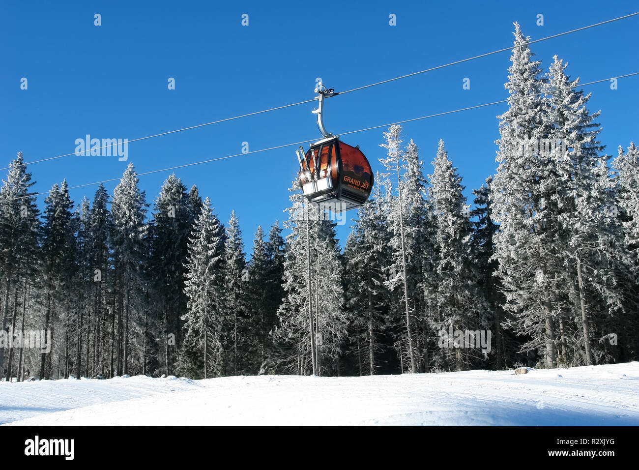 Jasna, Slovakia - January 25, 2017: Cabin of cableway on a background of snow-covered fir trees on a sunny day on the slopes of the Jasna ski resort,  - Stock Image