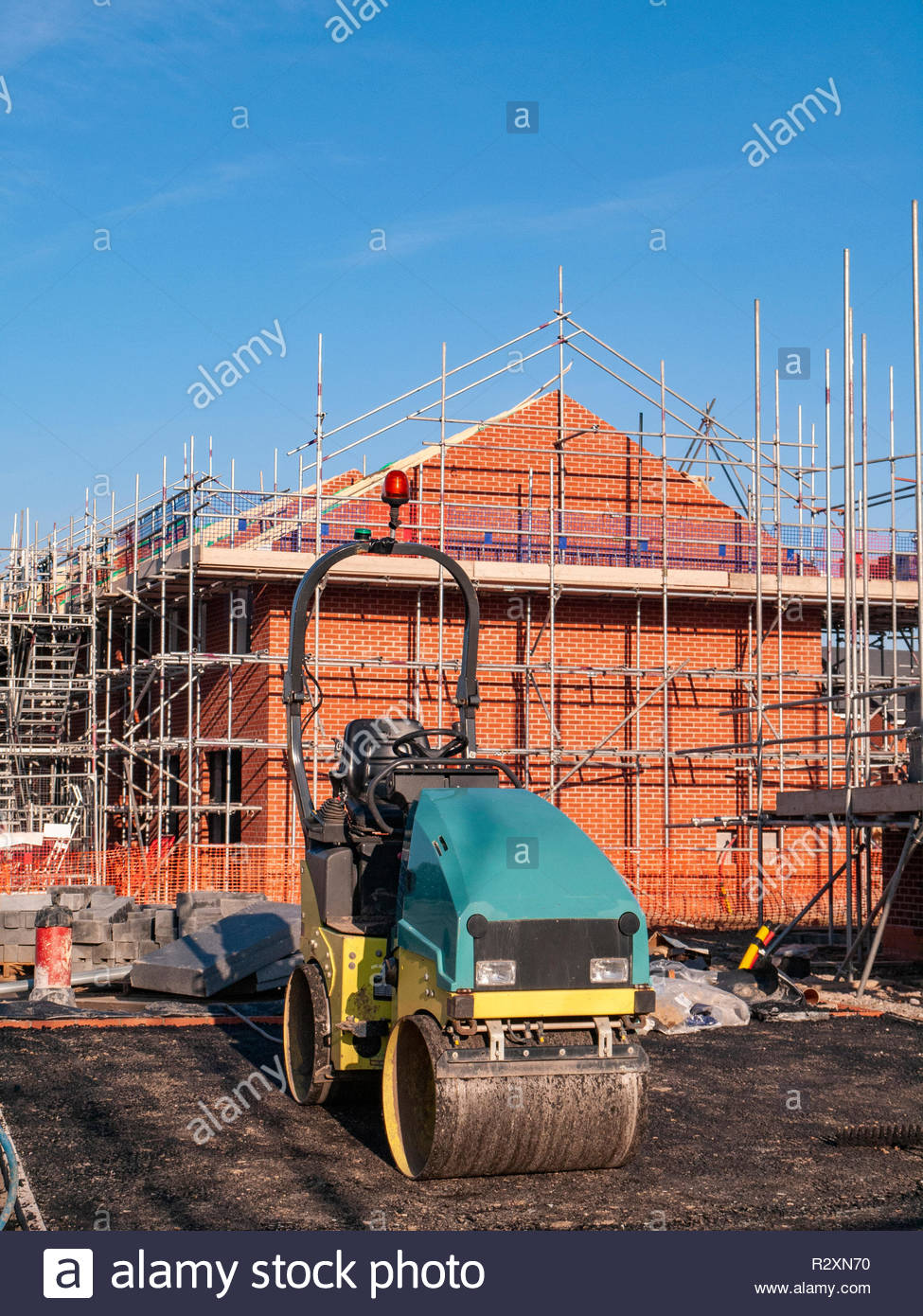 New build homes with equipment and in scaffolding on a new housing estate, Cheshire UK - Stock Image