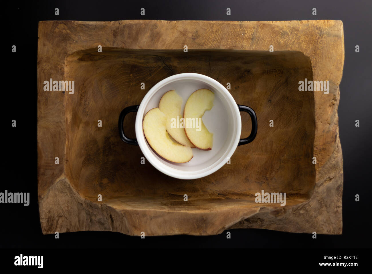 Breakfast on a wooden rectangular bowl with a black and white pot. - Stock Image