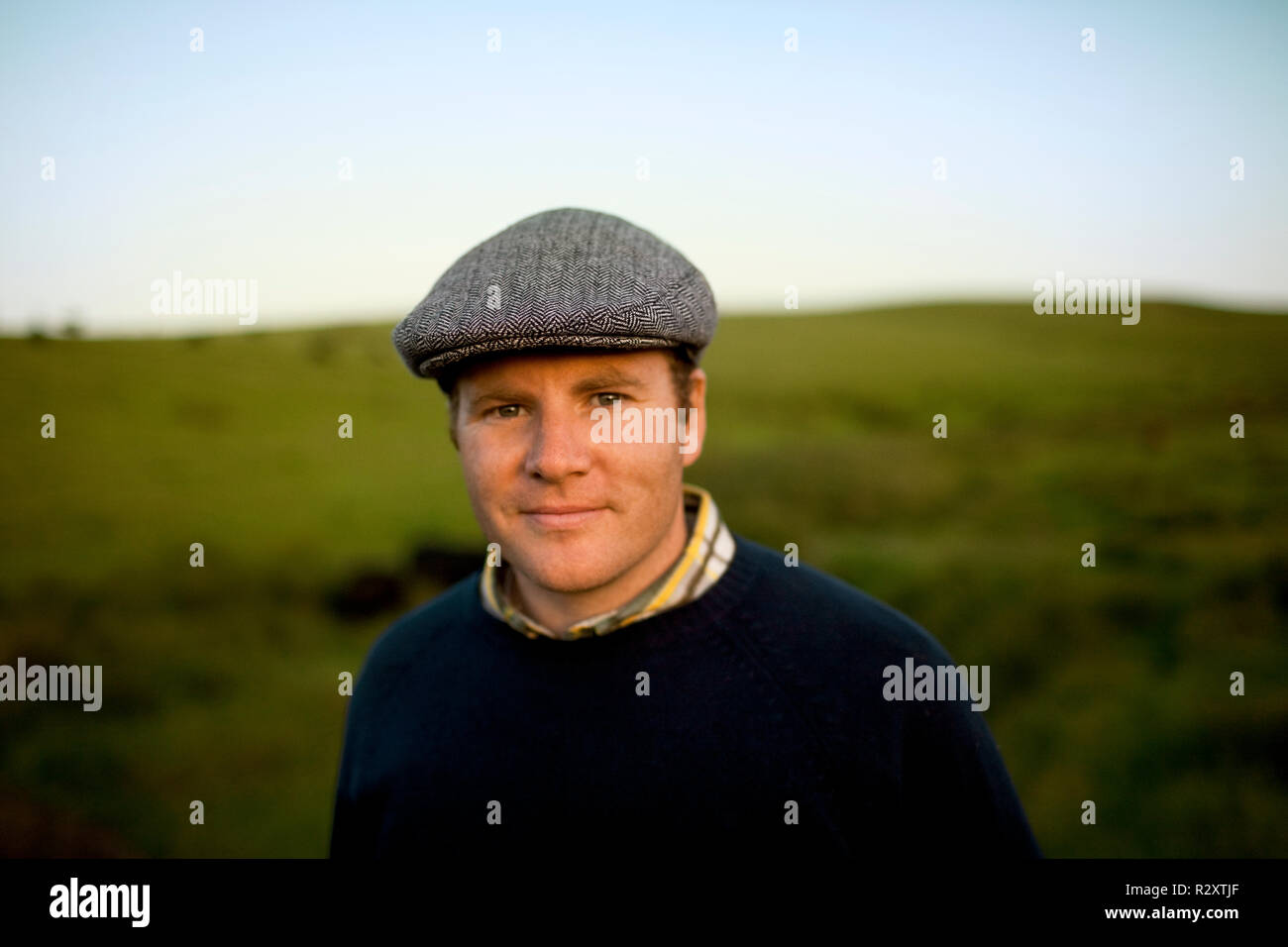 Portrait of a smiling mid-adult farmer wearing a tweed cap. - Stock Image