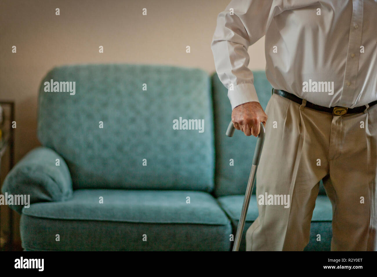 Elderly man stands up from a comfy couch with the help of his trusty walking stick. - Stock Image