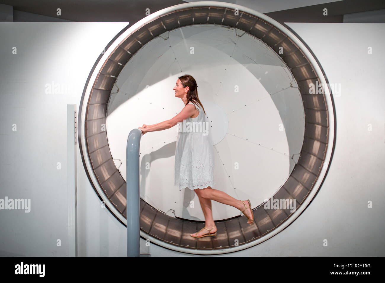Happy woman having fun int the hamster like wheel. The eternal wheel of live - Stock Image