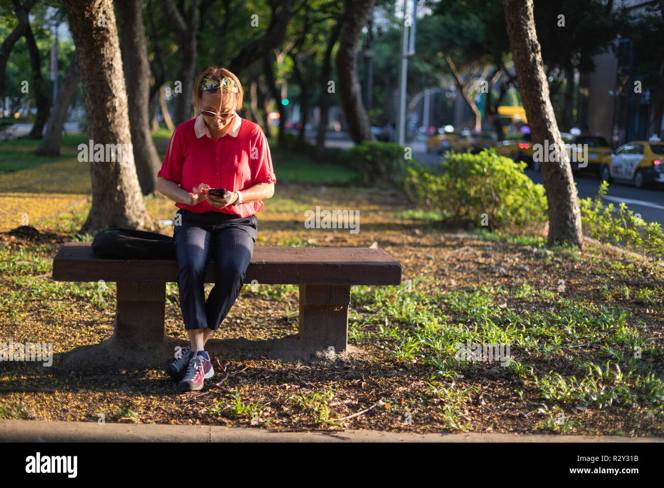 Mature Taiwanese Chinese woman sitting on a bench in an urban park looking at her mobile phone in the evening sun. - Stock Image