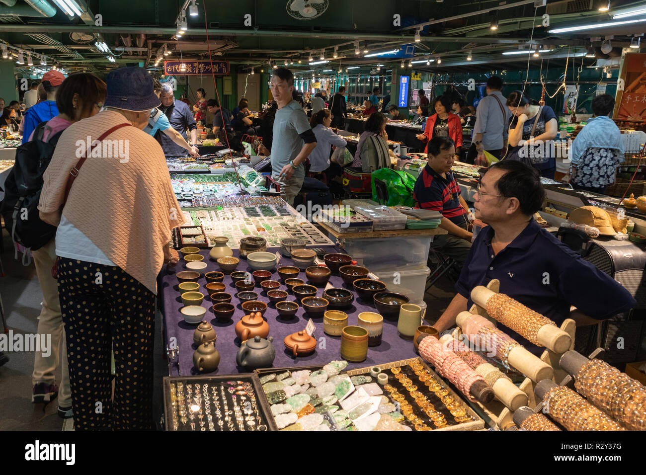 Visitors to the Jianguo Holiday Jade Market in Taipei peruse the goods being sold at the market. - Stock Image