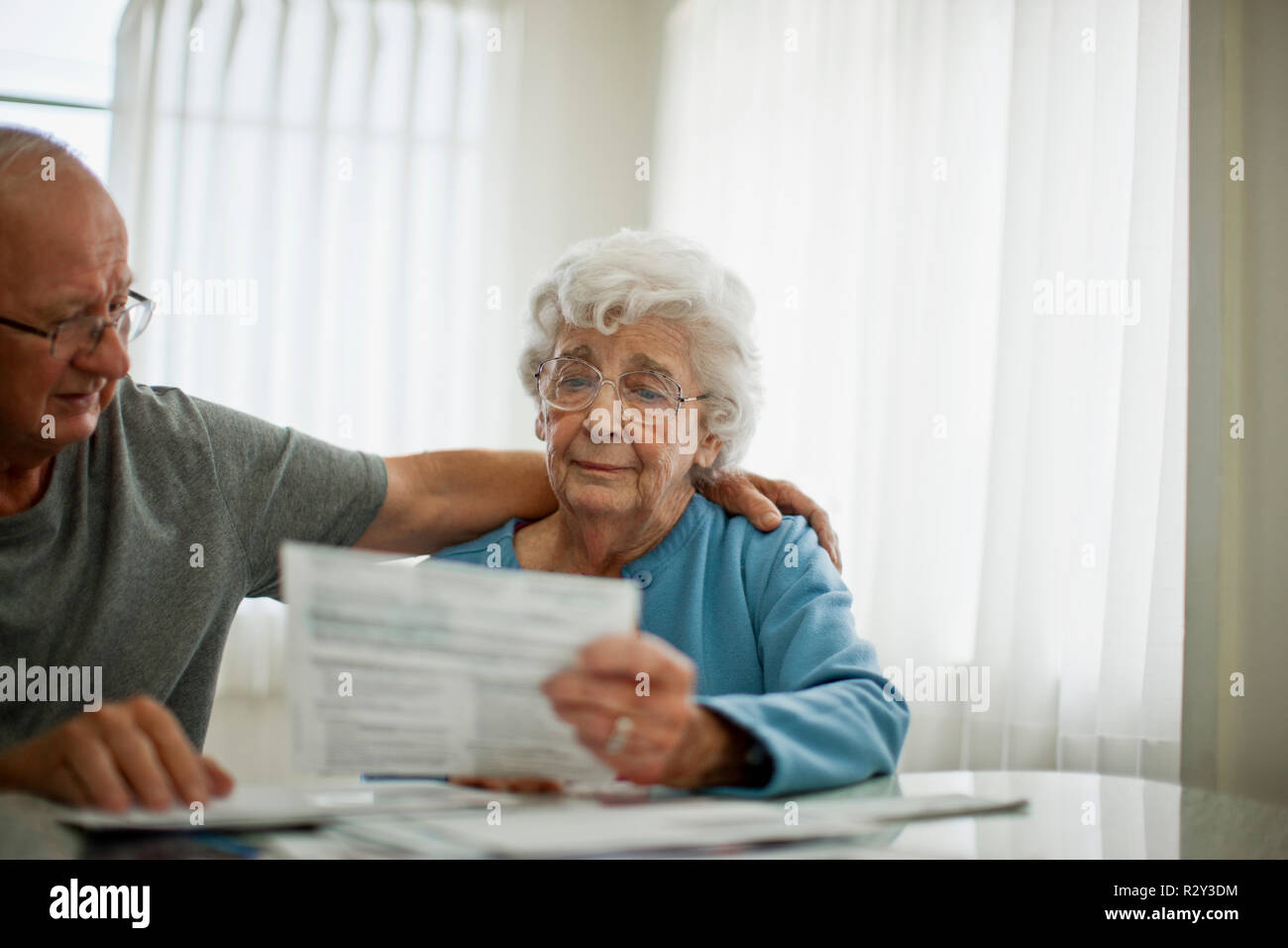 Anxious elderly couple try to comfort each other as they are worried about a bill that they have received. - Stock Image