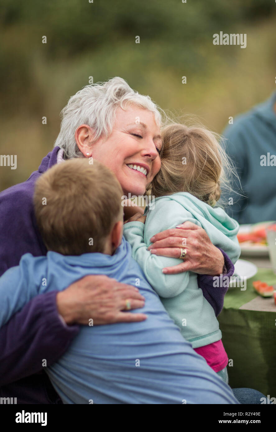 Affectionate grandmother hugs her young grandchildren. - Stock Image