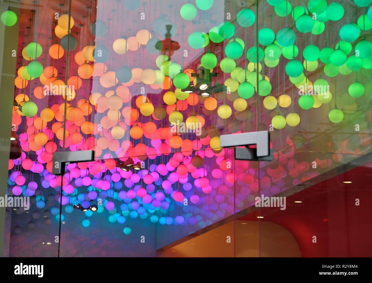 Varicoloured light bulbs hanging from above. - Stock Image