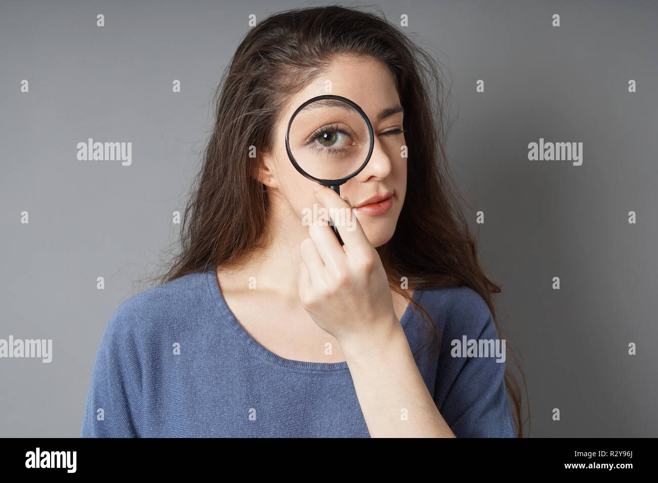 young woman looking through magnifying glass - detective spy audit search concept - Stock Image