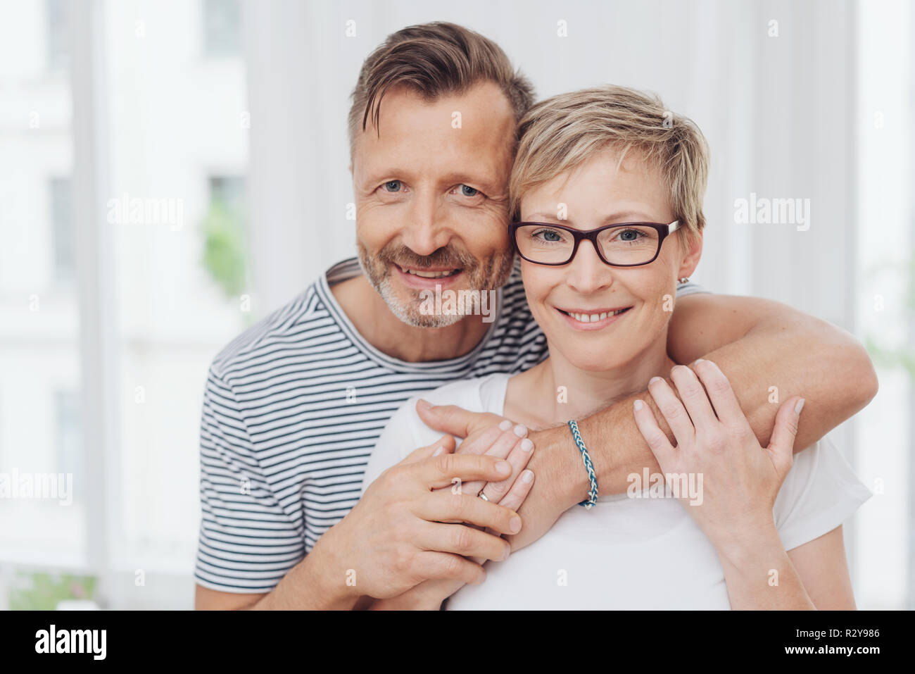 Upper body portrait of affectionate happy middle aged couple, man with arm around shoulder. - Stock Image
