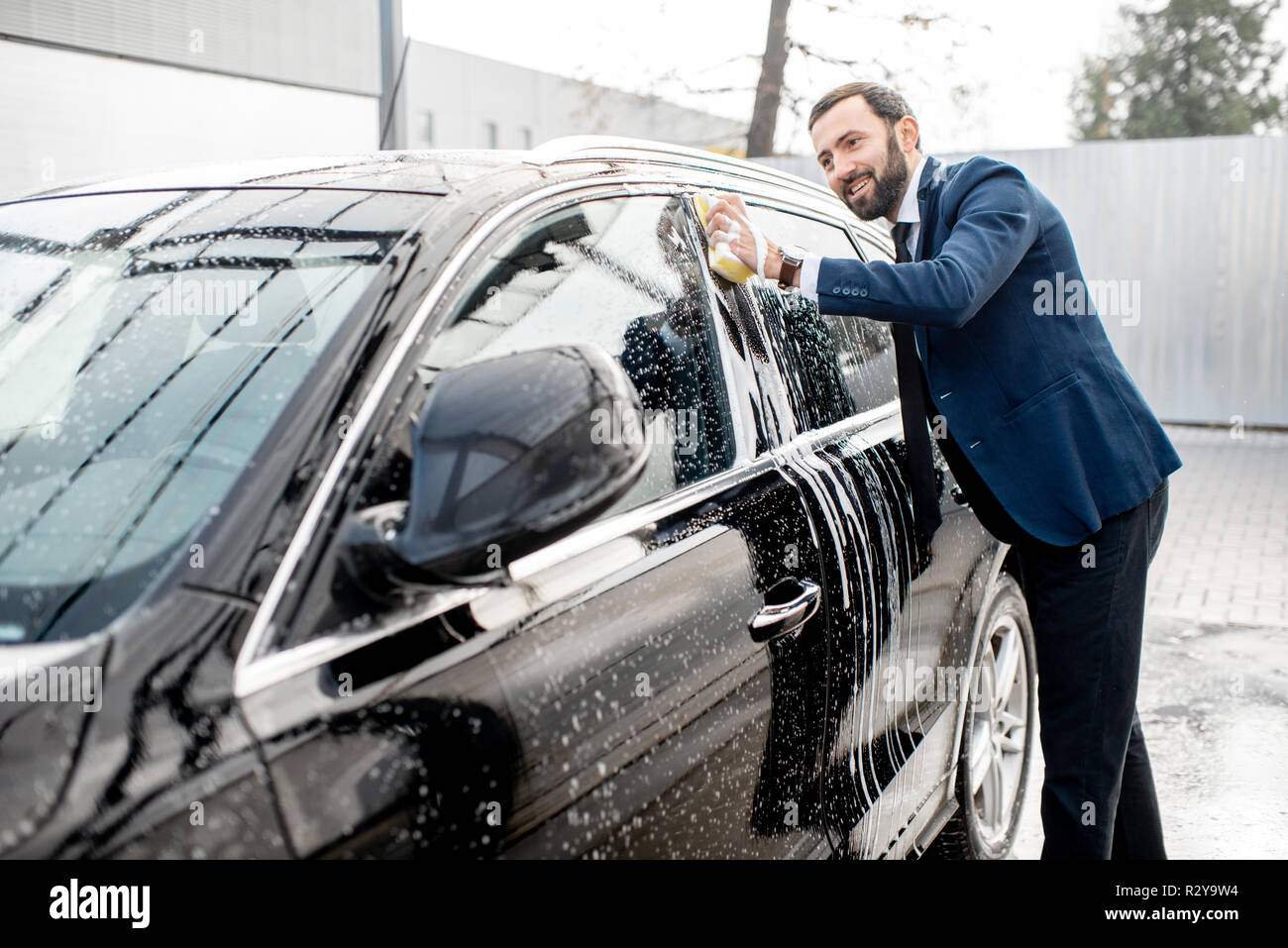 Elegant Businessman Dressed In The Suit Washing His Car With Yellow