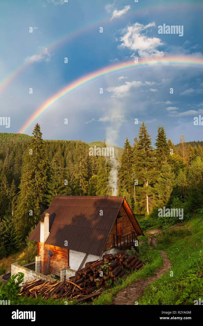 Beautiful house in mountain with forest and double rainbow on background. Travel background - Stock Image