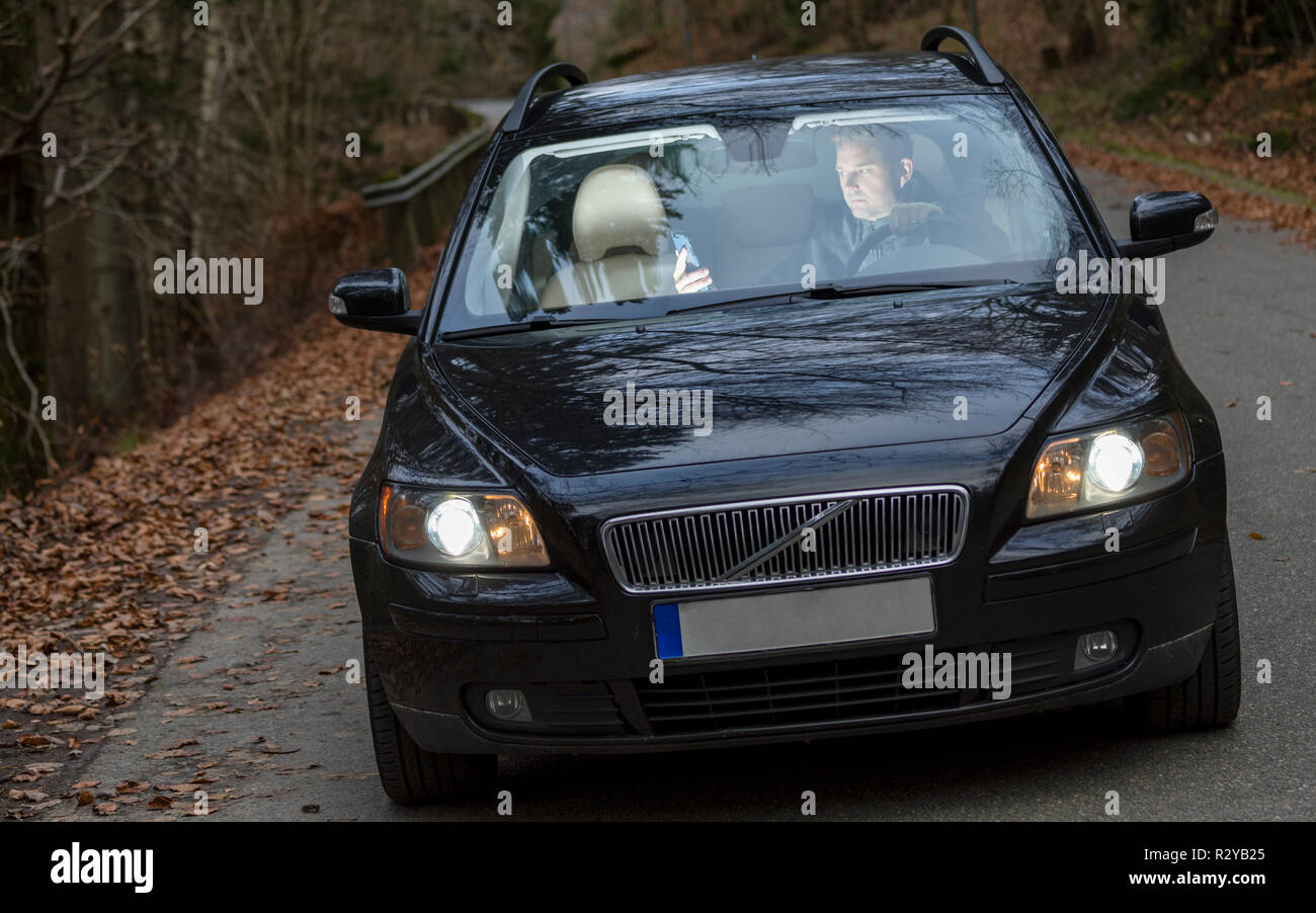Oncoming car with adult caucasian man driving car whilst looking down at and using mobile phone or smartphone with both hands - Stock Image