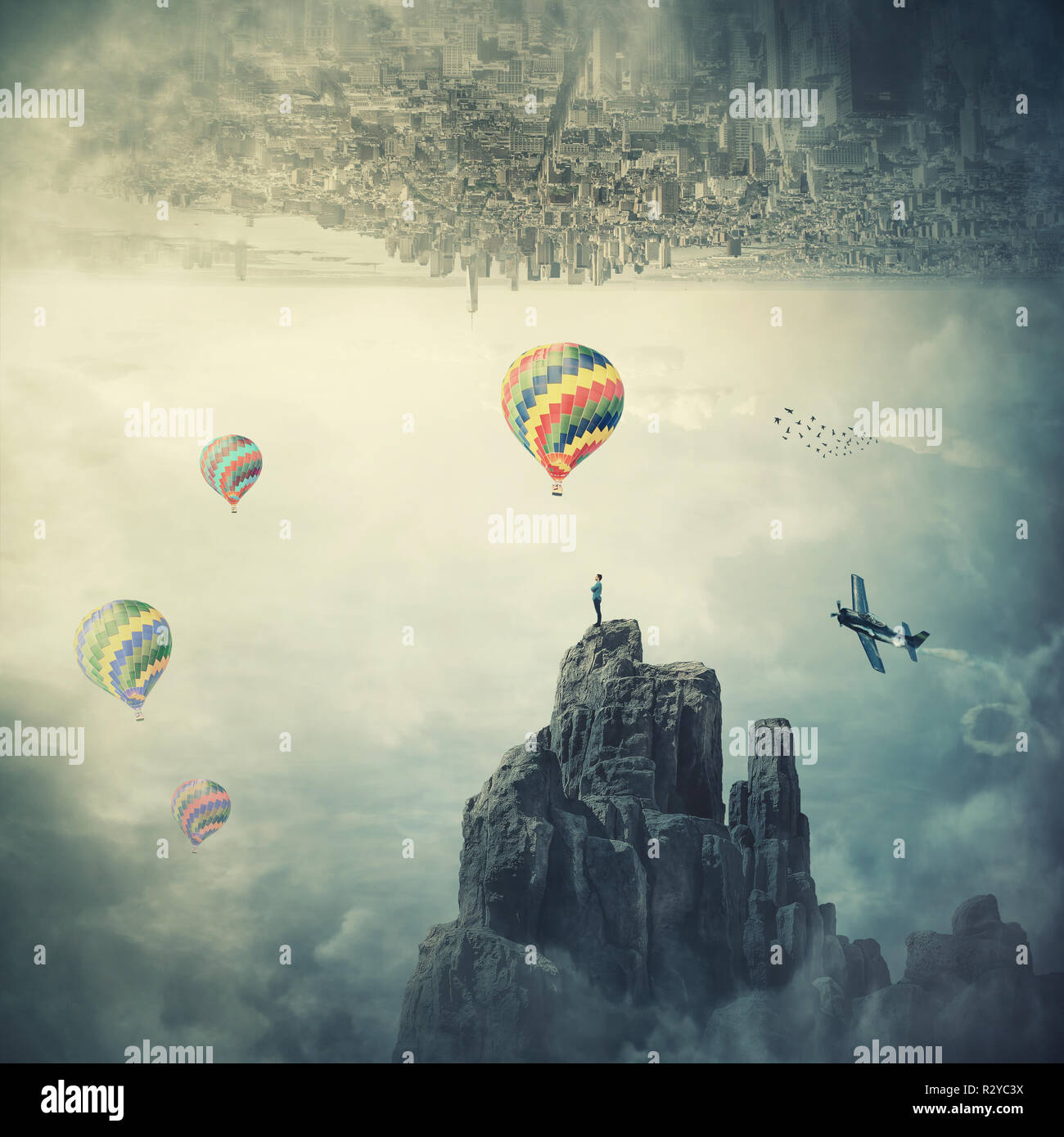 Man standing on the top of a mountain at the border of two parallel worlds a city above sky and hot air balloons flying. Beautiful mystical scene, ima - Stock Image
