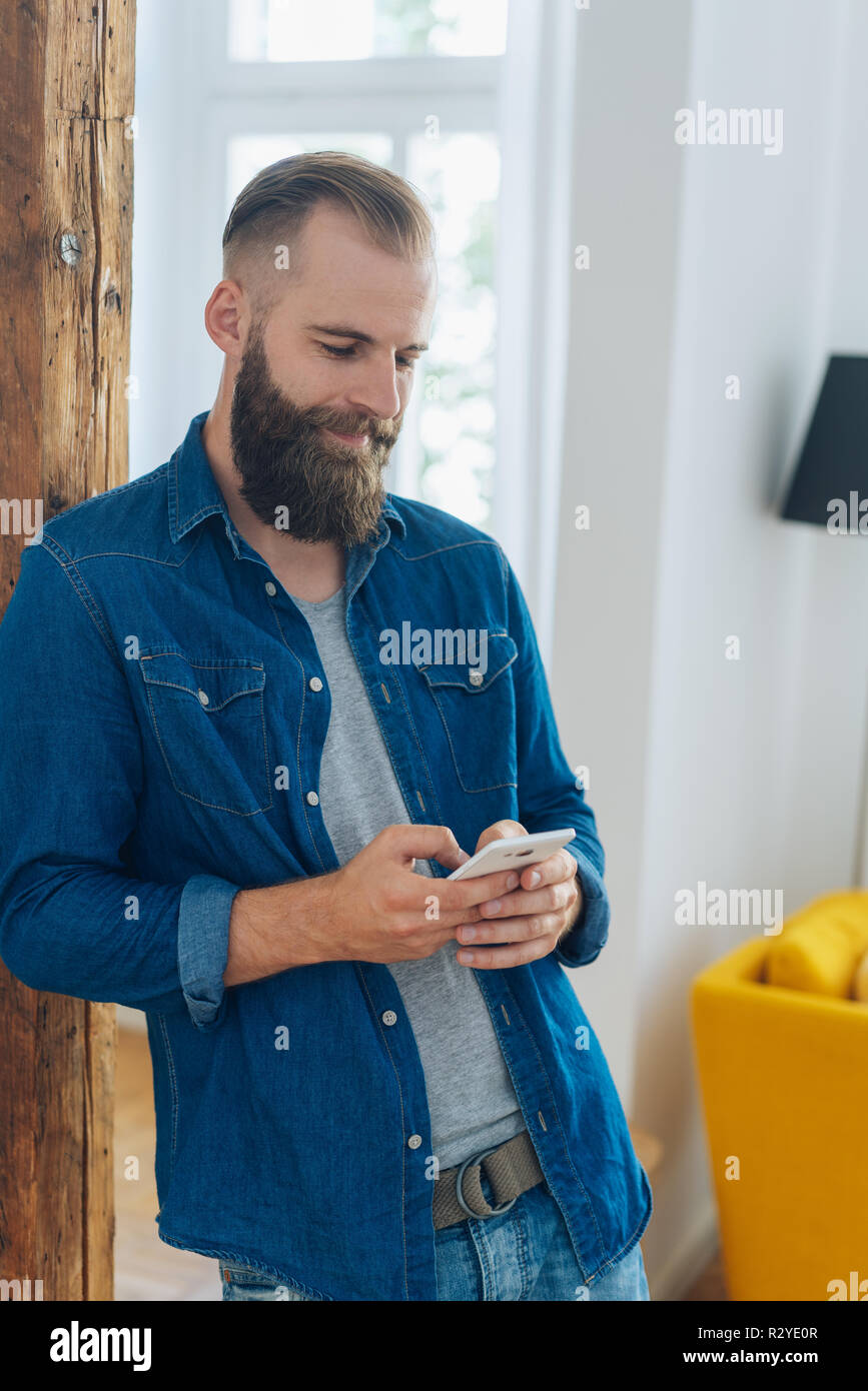Hipster Young Man With Beard And Short Hair Standing Indoors At Home Relaxing Against A Wooden Column Using His Mobile Phone Stock Photo Alamy