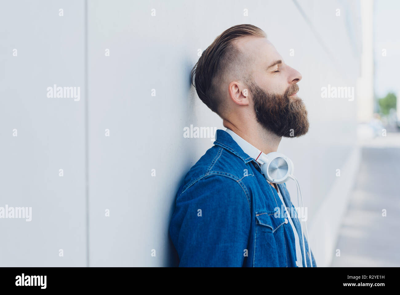 Bearded man taking a quiet moment to relax and de-stress leaning against a receding exterior white wall with eyes closed - Stock Image
