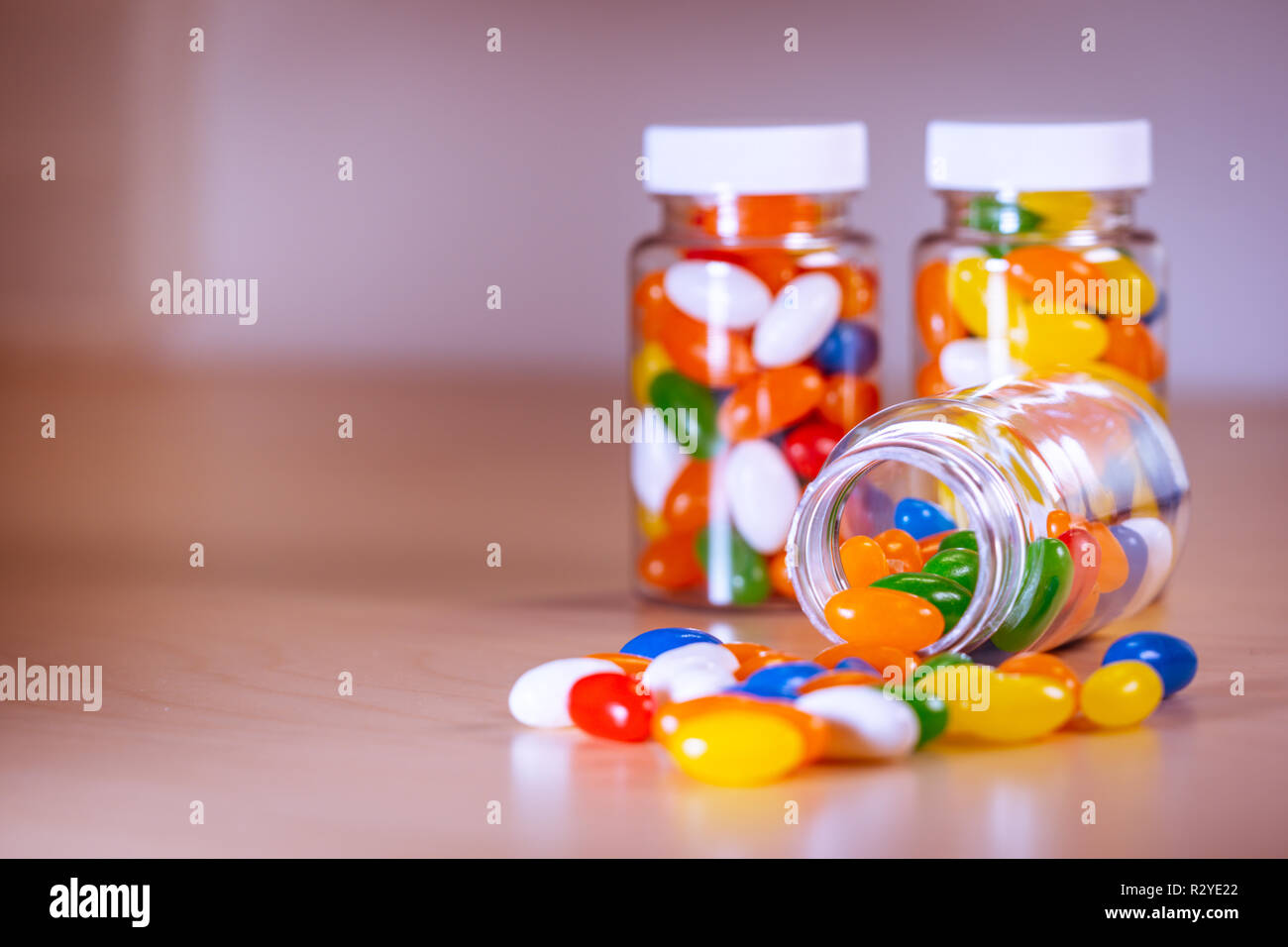 Multi-colored pills spilling out of a pill bottle against a blurry background - Stock Image
