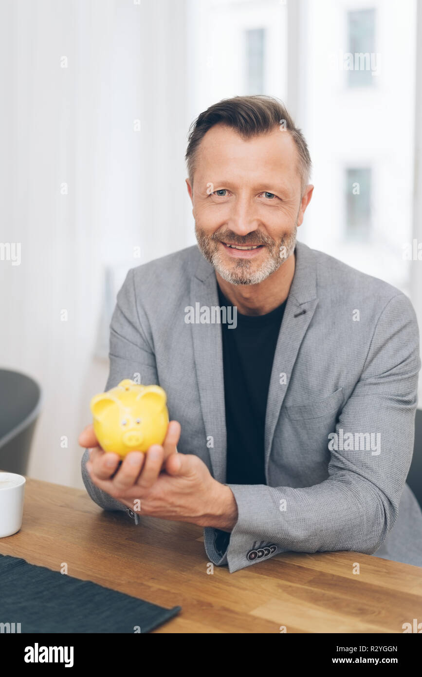 Portrait of smiling mature man wearing grey jacket holding yellow piggy bank while sitting at table Stock Photo