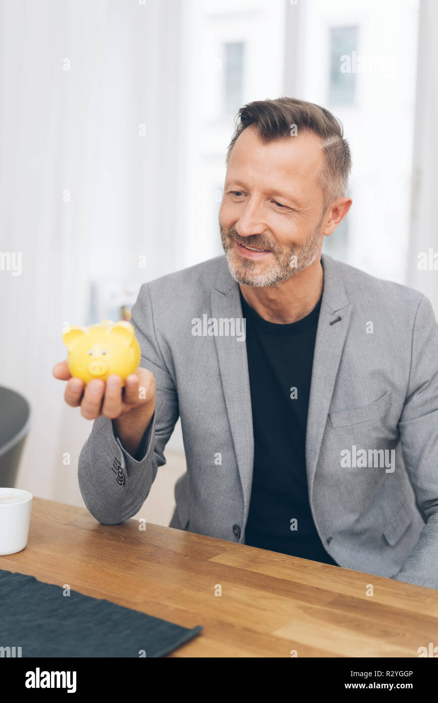 Portrait of smiling mature man wearing grey jacket holding yellow piggy bank at table Stock Photo