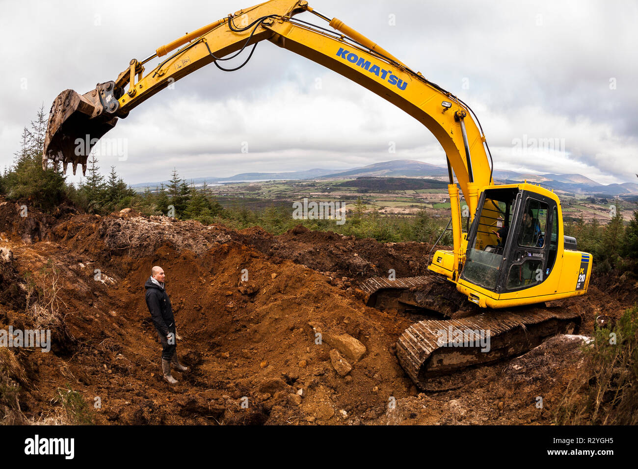 Komatsu excavator at work in a forest - Stock Image