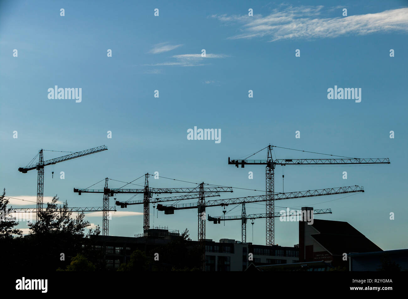 Silhouette of construction cranes against blue sky Stock Photo