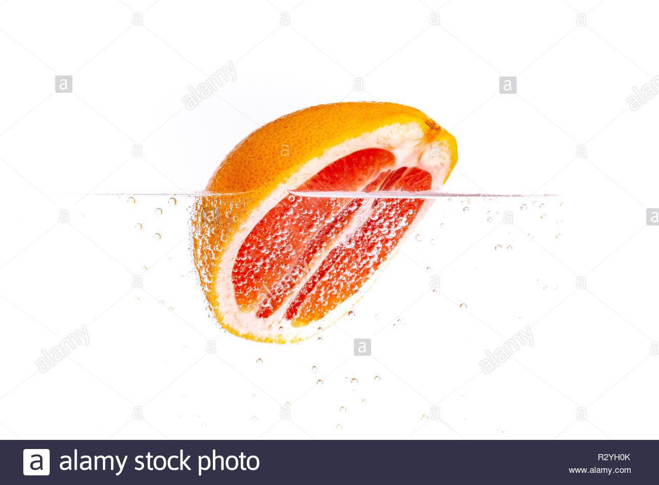Frische saftige halbe Grapefruit schwimmt im Wasser - Stock Image