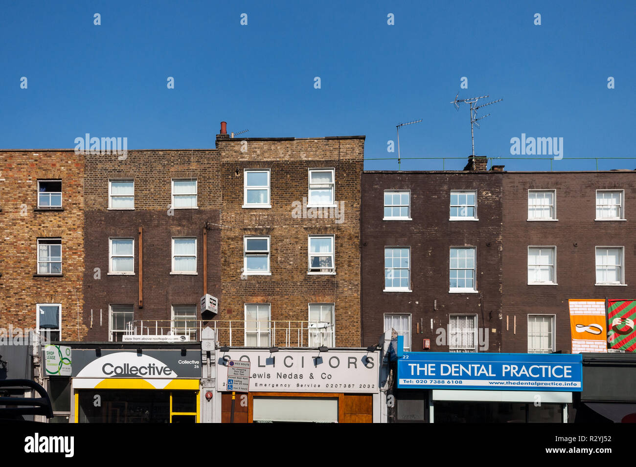 Terraced house facades and shop fronts in Camden Town, London - Stock Image