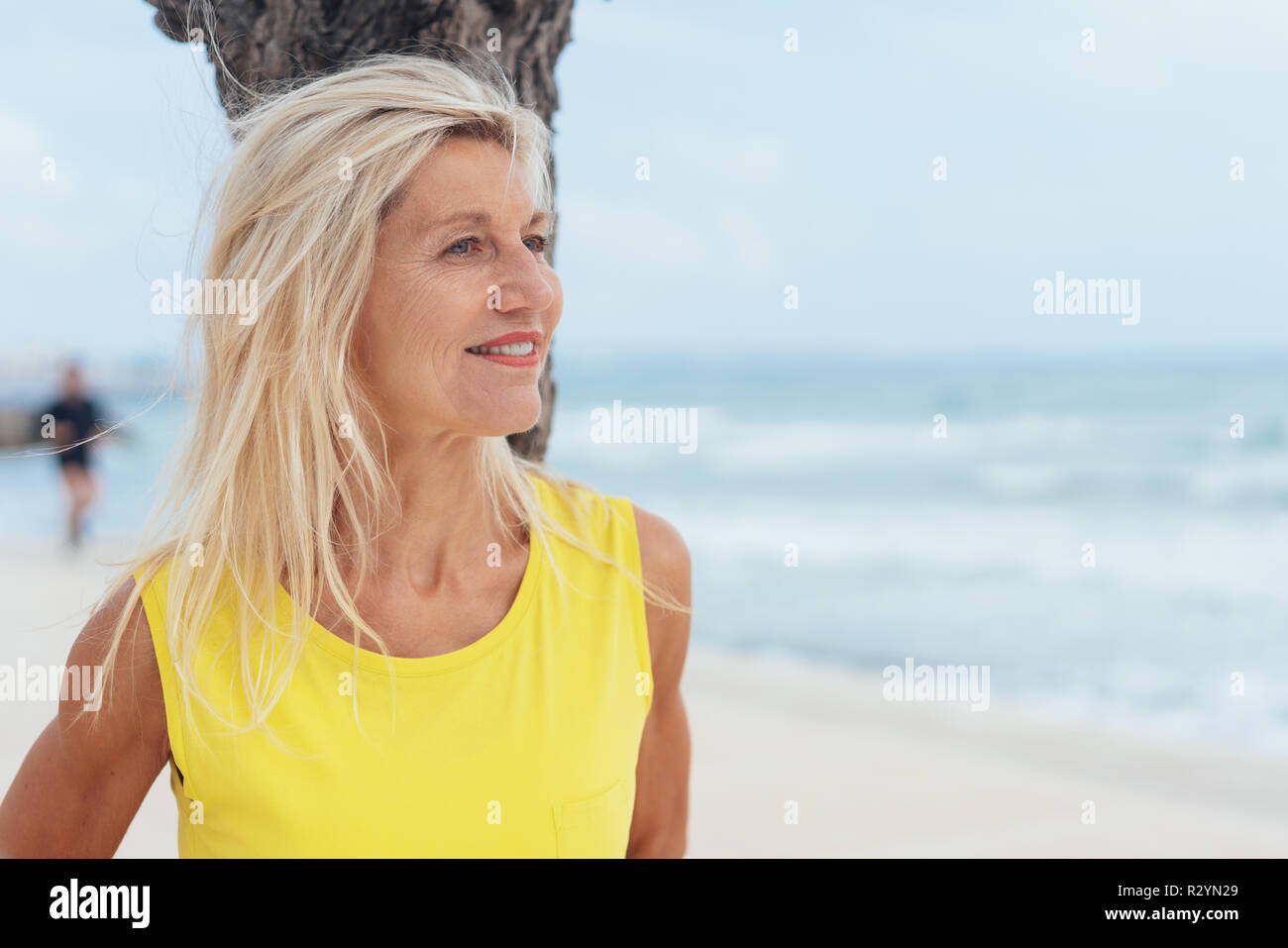 Attractive blond woman with her hair tousled by the sea breeze standing leaning against a tree enjoying a day at the seaside - Stock Image