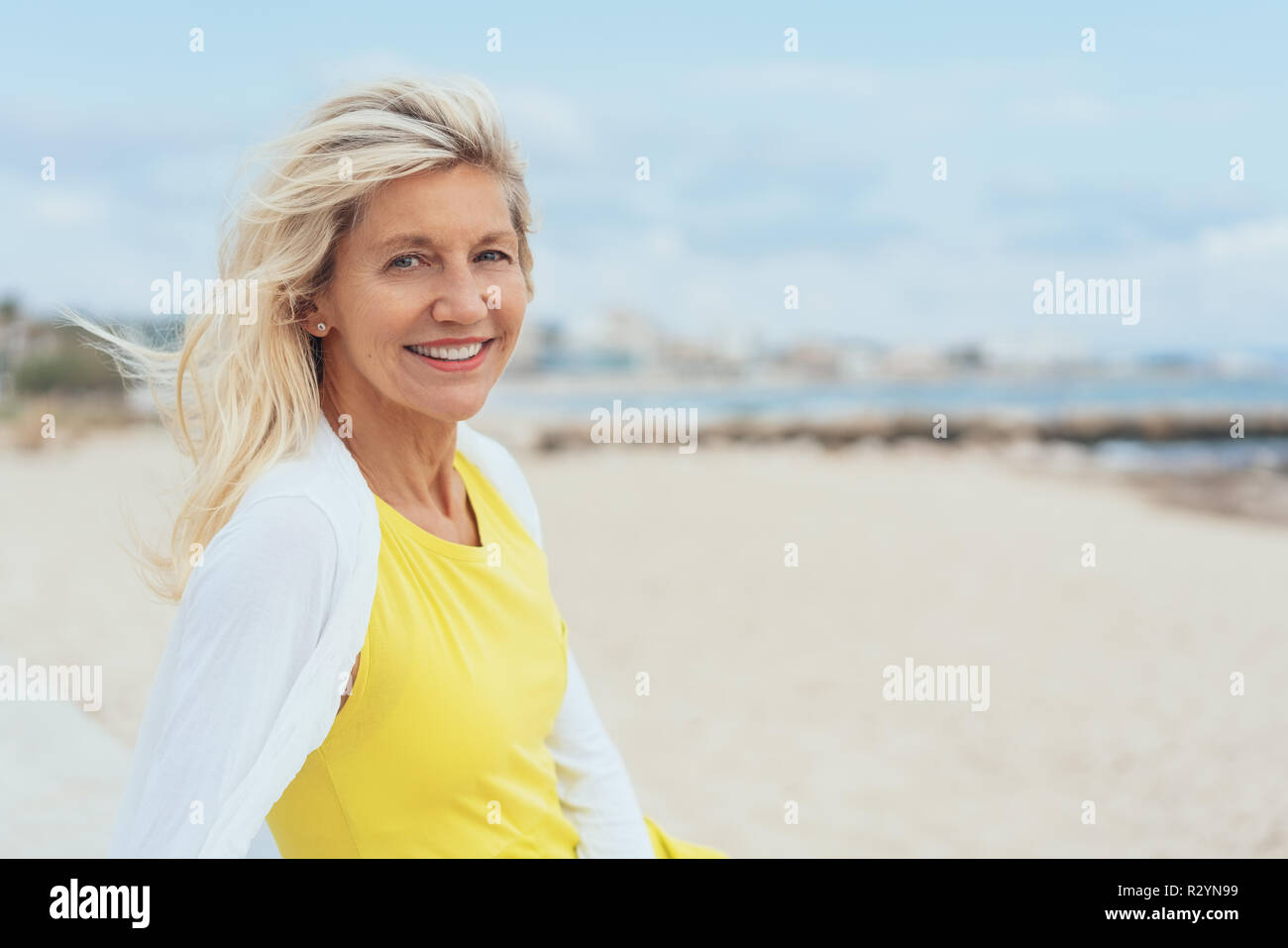 Attractive woman with tousled hair on a windy beach turning to smile at the camera with copy space - Stock Image